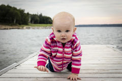 Little caucasian female crawling on the wooden pier. stock photo