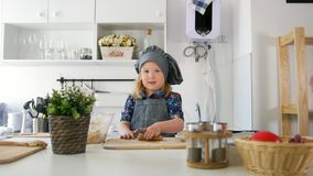 Little caucasian girl in apron rolls out the dough on the board. Close up stock video
