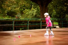 A little caucasian girl beginner roller in the autumn park in the rainy day. Rollerblading and outdoor activity concept stock image