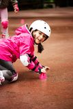 A little caucasian girl beginner roller falling on the ground in the autumn park in the rainy day. A little caucasian girl beginner roller falling on the ground stock image