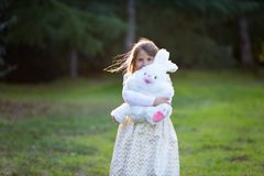 Little Caucasian girl with blond hair in white and golden festive dress running happily toward the camera, laughing, holding big p royalty free stock photography