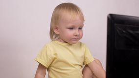 Little caucasian girl blonde looks into the computer laptop laughs and grimaces, close-up, emotions stock footage