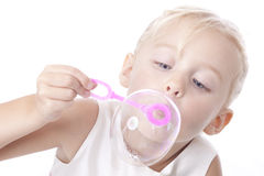 Little caucasian girl blowing soap bubbles. Little caucasian girl playing and blowing soap bubbles in a studio. isolated against white Stock Photo