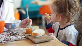 Little Caucasian girl, child, eating delicious bread and jam at a table in a cafe with her mother. Healthy and nutritious breakfast stock video