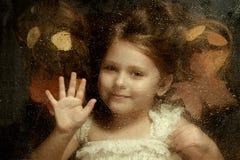 Little caucasian girl, close up portrait across a water drops Stock Photos