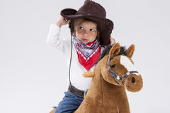 Little Caucasian Girl in Cowgirl Clothing Posing On Symbolic Horse Against White. Holding Her Stetson Stock Photos