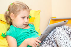 Little Caucasian girl with digital tablet pc Royalty Free Stock Photo