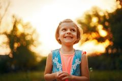 Little Caucasian girl with fair hair looking away and smiling. Five years old caucasian child girl with fair hair looking away and smiling outdoor at sunset Stock Photos