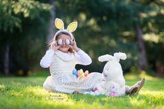 Little Caucasian girl in festive dress and bunny ears headband sitting on green grass and playing with Easter eggs and plush big b stock image