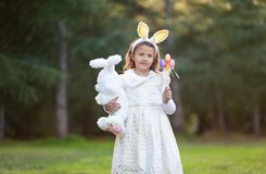Little Caucasian girl in festive dress with plush white toy bunny, looking to camera, smiling. royalty free stock photography