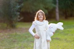 Little Caucasian girl in festive dress with plush white toy bunny, looking to camera, smiling. royalty free stock photo