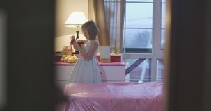 Little Caucasian girl holding casket and taking something red treasure from it. Cute child with her treasure. Door stock footage