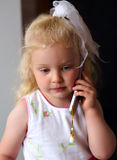 Little caucasian girl listening to mobile phone Stock Photo