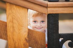 Little caucasian girl palaing hide and seek. 1 year old little caucasian girl palaing hide and seek game outdoors on sunny warm summer day. Closeup portrait of Stock Photos