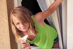 Little Caucasian girl with paper plane in the window Stock Photos