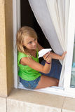Little Caucasian girl with paper plane in window Royalty Free Stock Photography