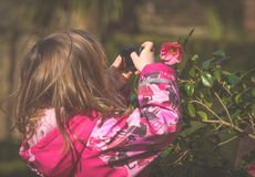 Little caucasian girl photographing flowers stock images
