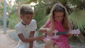 Little caucasian girl plays ukulele sit outdoor with african ethnicity best friend. Adorable pretty multi racial children 10s