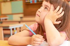 A child at a pensive tutorial looks up. Little Caucasian girl in school room sits at desk and looks up thoughtfully Royalty Free Stock Images