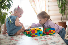 Little Caucasian girl sisters playing constructor on a table , Stock Photography