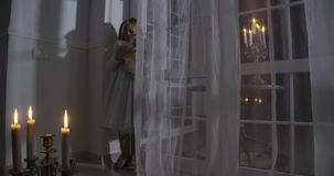 Little Caucasian girl standing in the corner in front of big window and holding doll. Child in candlelight playing with
