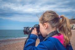 Little caucasian girl taking photographs on the beach stock images