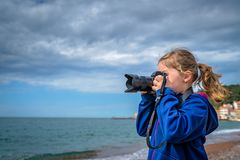Little caucasian girl taking photographs on the beach royalty free stock images