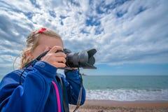 Little caucasian girl taking photographs on the beach royalty free stock photos