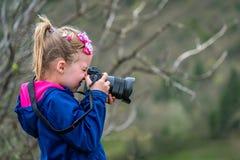 Little caucasian girl taking photographs stock photo