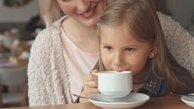 Little girl takes a sip of tea at the cafe stock images