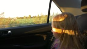 Little caucasian girl traveling in car. Car bounce and shake very much. Handheld shot close up. Little caucasian girl traveling in car. Car bounce and shake stock video