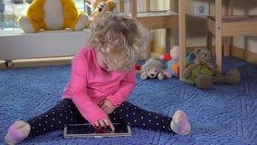 Little caucasian girl using tablet pc sitting on blue carpet stock video