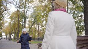 Little Caucasian girl in white hat and warm blue coat jumping in front of her grandmother walking along the alley. Mature woman in beige cloche hat and white stock video footage