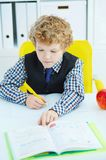 Little Caucasian schoolboy writing in a notebook sitting at a table . Red apple lies next to the table. Soon it`s lunch time royalty free stock images