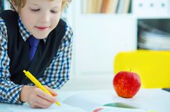 Little Caucasian schoolboy writing in a notebook sitting at a table . Red apple lies next to the table. Time for lunch. Little Caucasian schoolboy writing in a Royalty Free Stock Photography