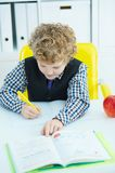 Little Caucasian schoolboy writing in a notebook sitting at a table . Red apple lies next to the table. Soon it`s lunch time royalty free stock photos