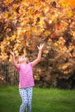 Girl catching falling leaves in autumn. Little Caucasian toddler girl catching colorful falling leaves in a park in autumn royalty free stock images