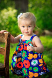 Little caucasian toddler stands using chair for support outside royalty free stock image