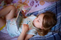 Little Caucasian two-year-old girl lying on a plaid pillow and watching cartoons on a tablet computer. modern technology. Little Caucasian two-year-old girl stock photo