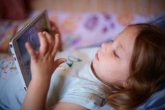 Little Caucasian two-year-old girl lying on a plaid pillow and watching cartoons on a tablet computer. modern technology. Little Caucasian two-year-old girl royalty free stock image