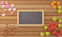Little chalkboard surrounded by fruits and cookies. Valentines theme and wooden floor Stock Photography