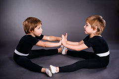 Little champions. Two twins little girls, dressed in gymnastic costumes and doing stretching Royalty Free Stock Image
