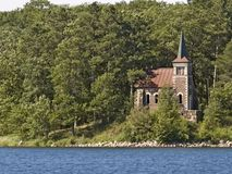 Little Chapel by the Lake. Small stone/brick chapel in woods next to lake with person sitting on shore reading Stock Photos