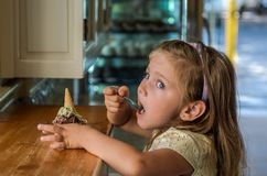 Little charming baby girl eating gelato ice cream in a cafe.  royalty free stock image