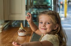 Little charming baby girl eating gelato ice cream in a cafe.  stock photo