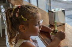 Little charming baby girl eating ice cream in the cafe.  royalty free stock photos