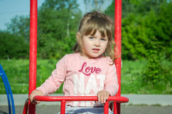 Little charming baby girl playing on a playground, riding on a swing on a bright sunny day Stock Images