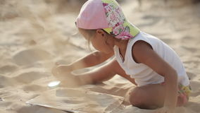 Little charming baby girl playing with sand without toys stock video footage