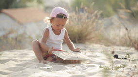 Little charming baby girl playing with sand without toys stock footage