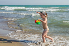 Little charming baby girl playing on the sea beach with a watering can. Picking up water from the sea, a bright sunny hot day Stock Photo